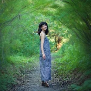 портрет девушки на фоне зеленого туннеля из листьев