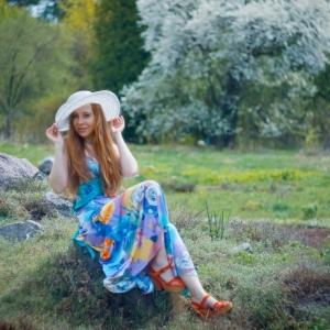 девушка в белой шляпе на фоне цветущего дерева
