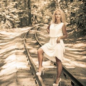 лесной портрет девушки на фоне уходящих в даль рельсов