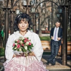 Невеста со свадебным букетом в руках и жених, стоящий на дальнем плане